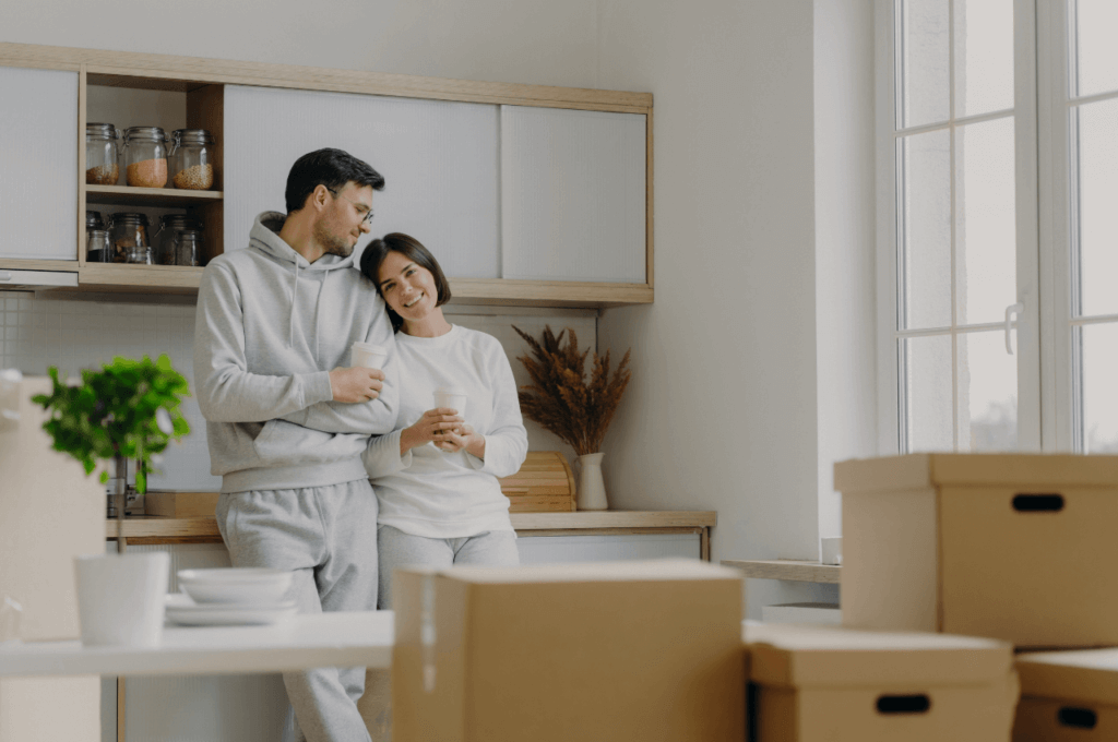 A couple in their kitchen surrounded by moving boxes.